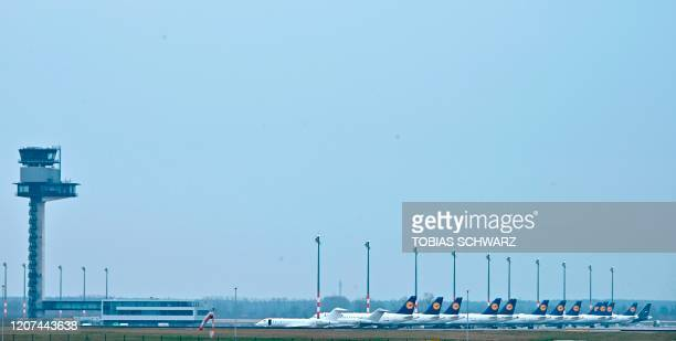 Aircrafts of German airlineLufthansa are parked at the BER airport site near Berlin on March 17, 2020. - German airline group Lufthansa on March 16,...