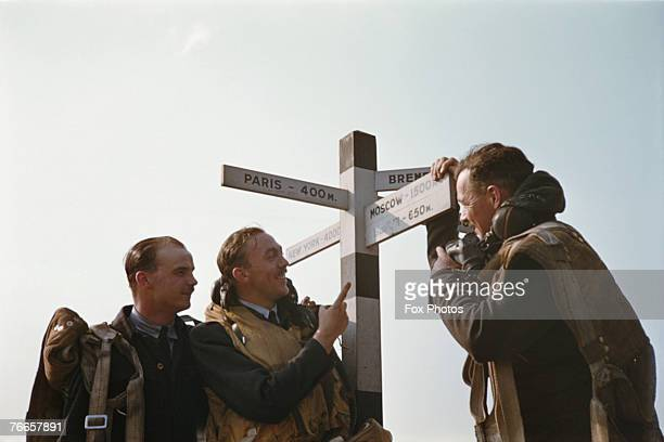 RAF aircrew at a British airfield point to a humorous signpost indicating Paris Moscow New York Berlin and Bremen circa 1943