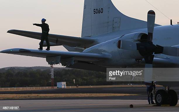 Aircrew walk on the wing of a Japanese Air Force AP3C Orion after it landed at RAAF Pearce Base to join the search for missing Malaysian Airlines...