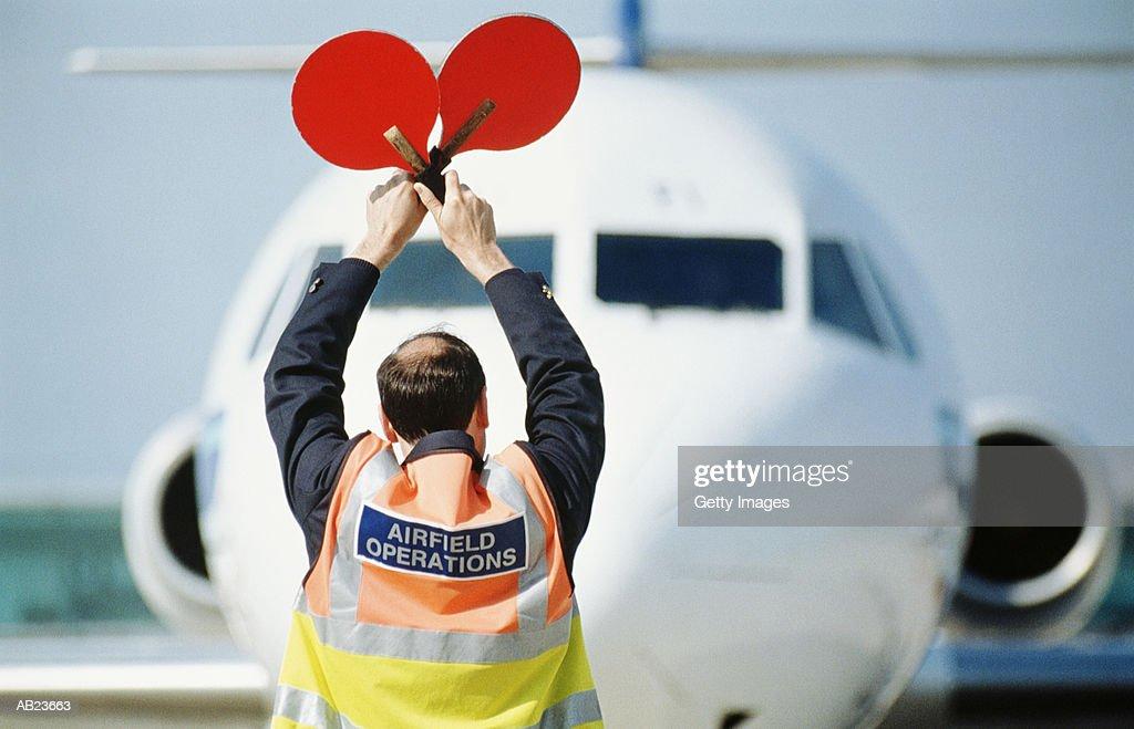Airfield operator signaling to airplane : Stock Photo
