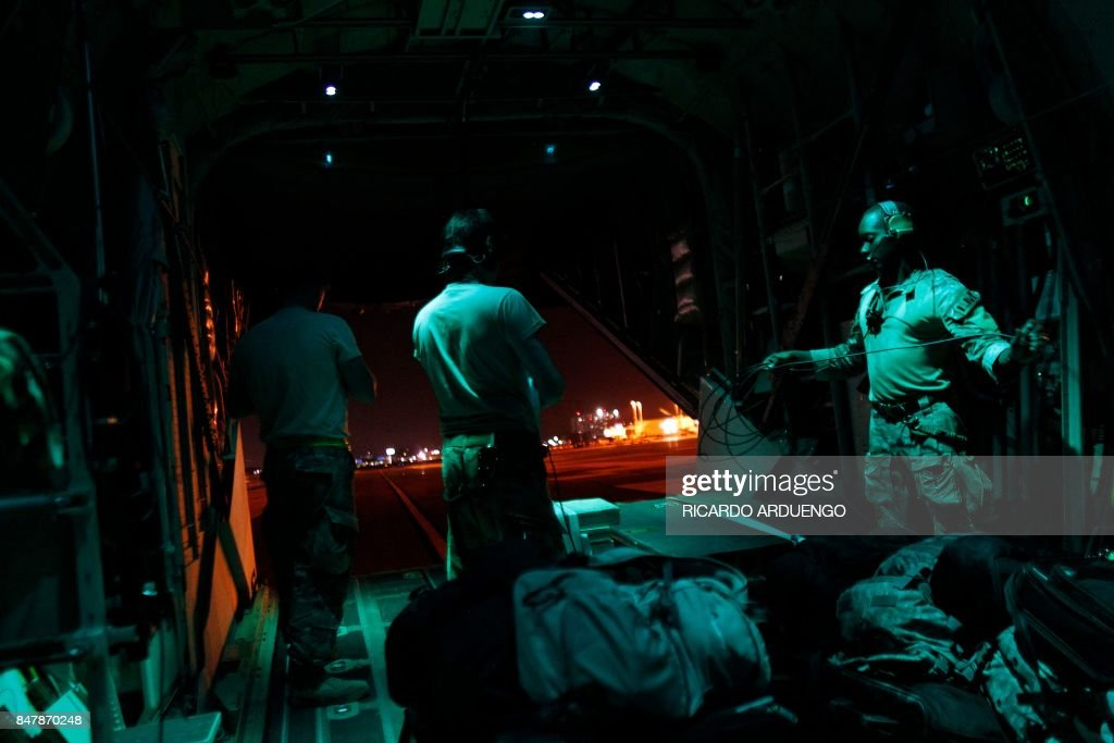 Airforce crew members stand on the back of a C-130 cargo plane while taxiing at the Luis Munoz Marin Puerto Rico International Airport after delivering supplies to the Caribbean island which sustained extensive damage after the passing of Hurricane Irma in San Juan, on September 15, 2017. / AFP PHOTO / Ricardo ARDUENGO