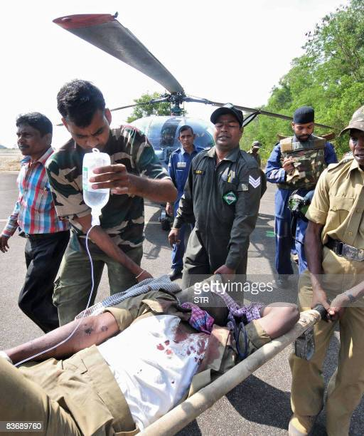 Airforce personel move an injured Border Security Forces soldier from a helicopter at an airfield in Raipur on November 14 2008 Indian security...