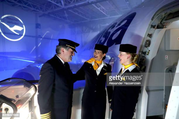 Airhostesses and a pilot of German airline Lufthansa stands a the main door of Lufthansa's first Airbus A350900 passenger plane during a rollout...