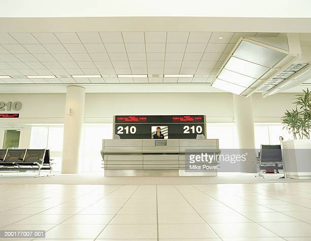 Airline attendant at check-in counter, low angle view