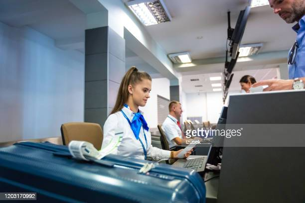 airline attendant doing check-in for flight at airport - crew stock pictures, royalty-free photos & images