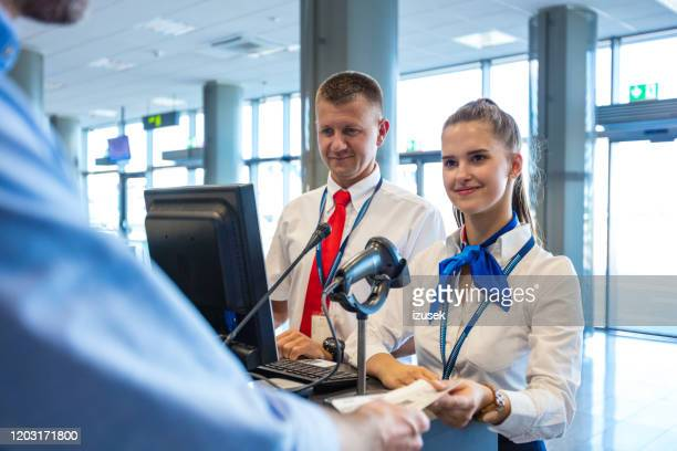 airline attendants doing boarding for flight at airport - izusek stock pictures, royalty-free photos & images