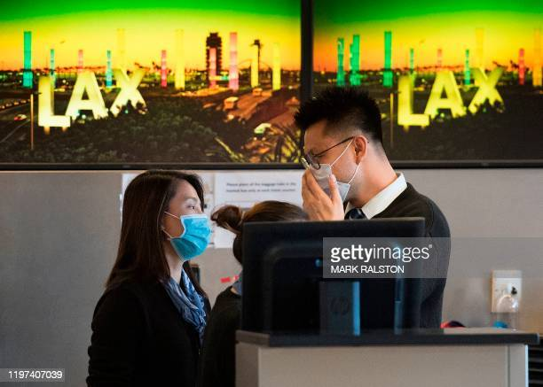 Airline check in staff wear face masks to protect against the spread of the Coronavirus at the Los Angeles International Airport California on...