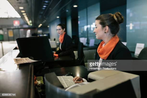 Airline Check-In Attendant sitting at counter