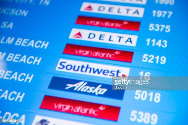 航空会社は空港の兆候で便名を表示します。 - 南西 ストックフォトと画像
