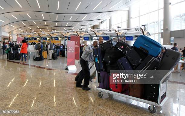 Airline employees move luggage at the international counter the day following a major power outage caused by a fire at HartsfieldJackson Atlanta...