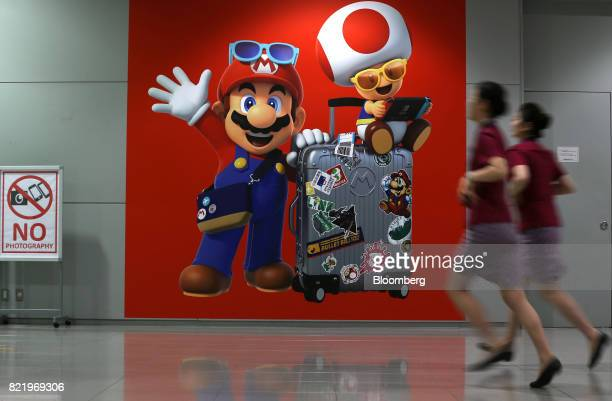 Airline employees run past a mural featuring Nintendo Co's Mario left and Toad video game characters at Terminal 1 of Kansai International Airport in...