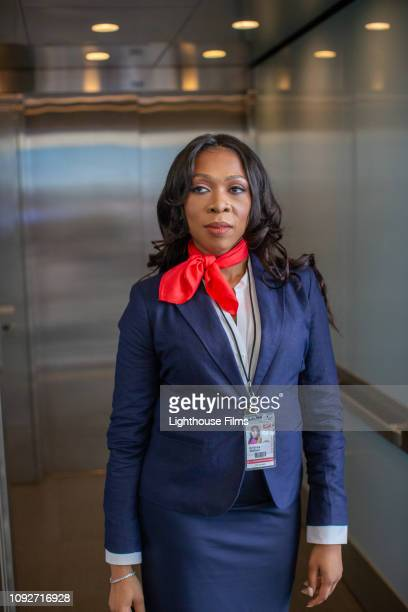 Airline flight attendant stands in airport elevator.