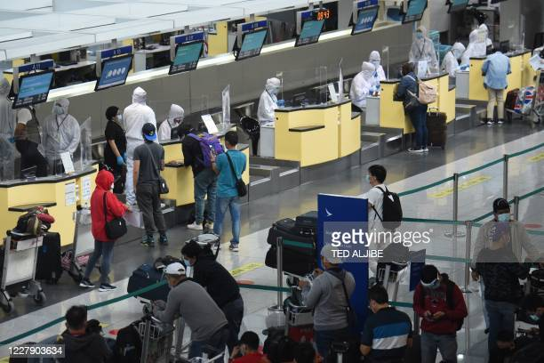 Airline ground staff wearing protective gear work at the counter at the airport in Manila on August 4, 2020. - More than 27 million people -- a...