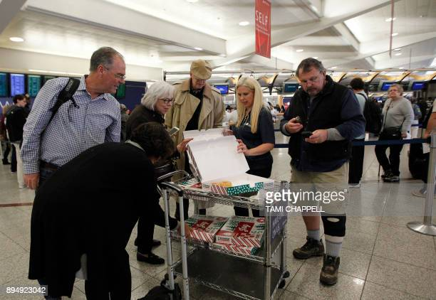 Airline passengers are handed donuts as they pass through or wait in line along the Delta Airlines counter the day following a power outage caused by...