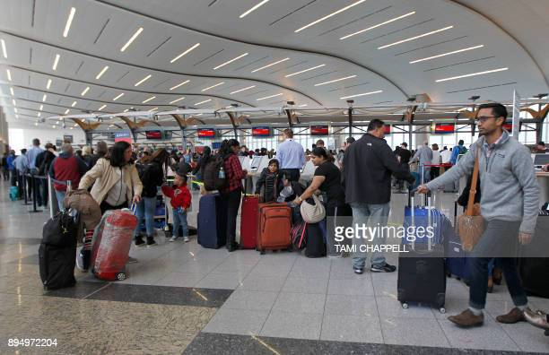 Airline passengers arrive to stand in line at the Delta Airlines international counter the day following a power outage caused by a fire at...