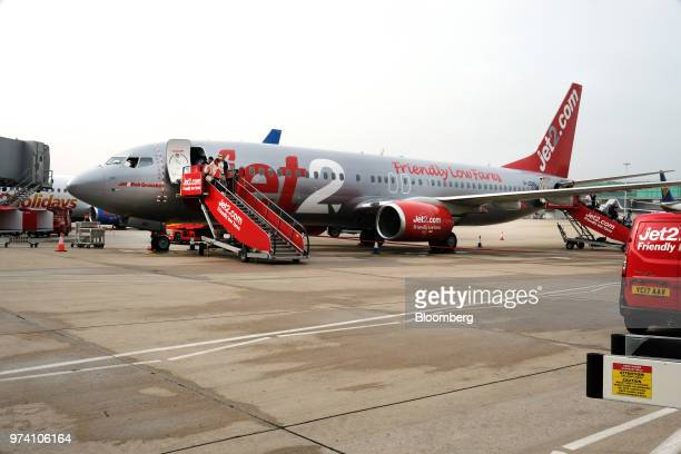 Airline passengers disembark from a Jet2 aircraft, a Boeing 737 named 'Jet2Bob Gruszka', owned by Dart Group Plc, as the plane sits on the tarmac at...
