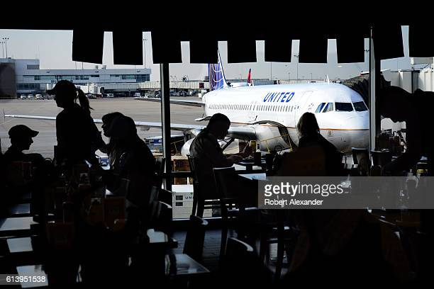 Airline passengers eat in a terminal cafe as a United Airlines passenger plane is parked at a gate at Denver International Airport in Denver Colorado