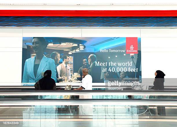 Airline passengers move past a poster for Emirates Airlines as they travel along a moving walkway inside terminal 3 at concourse A the new A380...