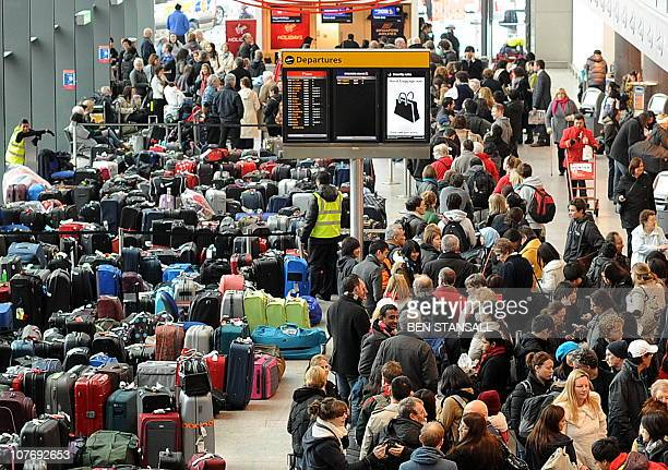 Airline passengers queue beside rows of luggage items in Heathrow airport's Terminal 3 west of London on December 20 2010 The boss of British...