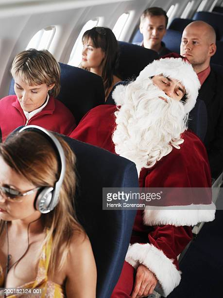 airline passengers relaxing in seats, man dressed as santa sleeping - christmas plane stock pictures, royalty-free photos & images
