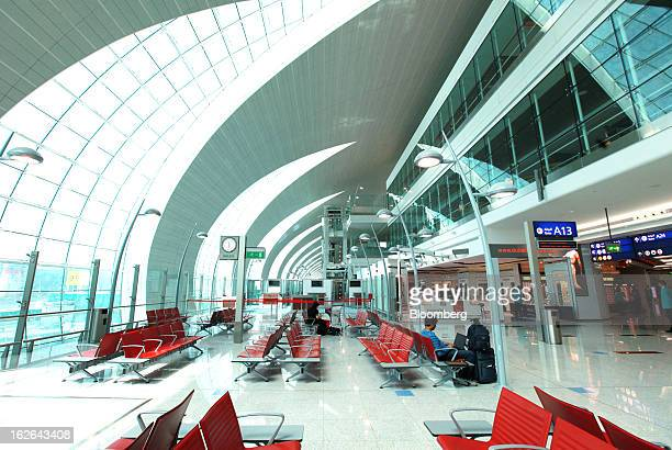 Airline passengers sit and wait near gate 'A13' inside terminal 3 at concourse A the new A380 terminal at Dubai International Airport in Dubai United...