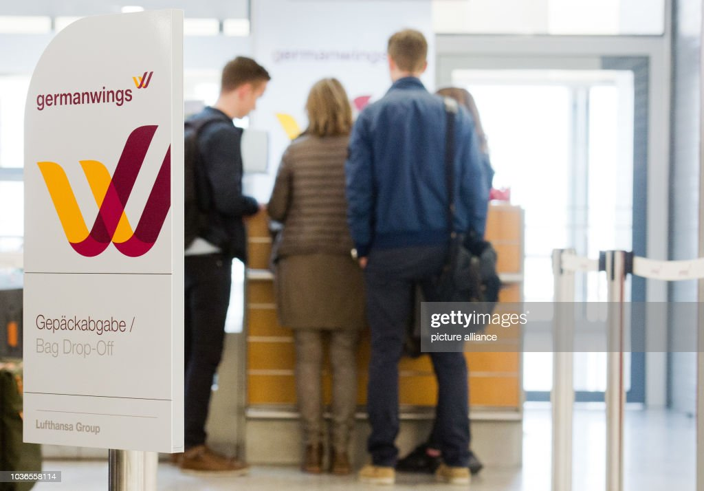 Airline Passengers Stand At The Germanwings Check In Counter At The