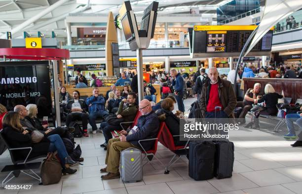 Airline passengers wait for their flight departures March 13 2014 at London England's Heathrow Airport in Terminal 5