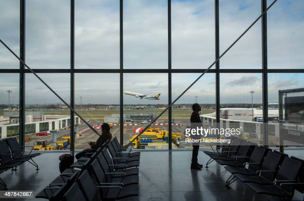 Airline passengers wait for their flights February 19 2014 as a Lufthansa flight takes off at Heathrow International Airport in London England