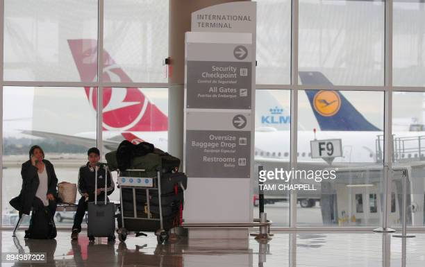 Airline passengers wait in front of a Turkish Airlines plane at the International terminal the day following a power outage caused by a fire at...