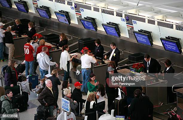 Airline passengers wait in line at the American Airlines ticket counter in Terminal D at Dallas/Fort Worth International Airport December 27 2009 in...