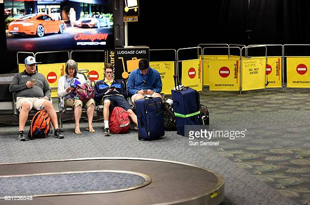 Airline passengers wait in Terminal 2 as large black curtains and barriers block the area where Friday's fatal shooting took place at Fort...