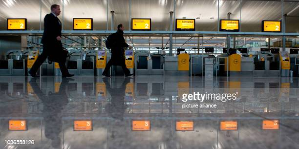 Airline passengers walk past empty checkin counters at the airport in Munich Germany 19 March 2015 The Lufthansa pilots' strike continues The...