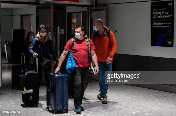 Airline passengers wearing face masks leave baggage reclaim when they arrive at Heathrow Terminal 5 as the outbreak of coronavirus intensifies on...