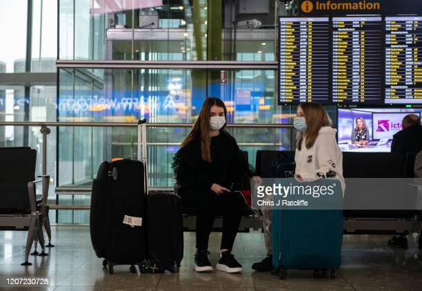 Airline passengers wearing face masks sit with their bags at departures at Heathrow Terminal 5 as the outbreak of coronavirus intensifies on March...