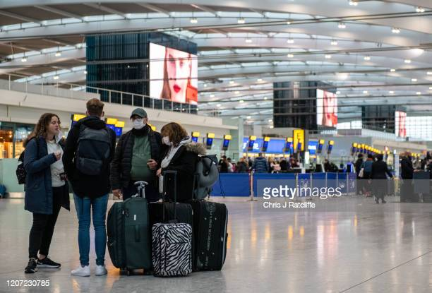 Airline passengers wearing face masks wait to check in their bags at Heathrow Terminal 5 departures as the outbreak of coronavirus intensifies on...