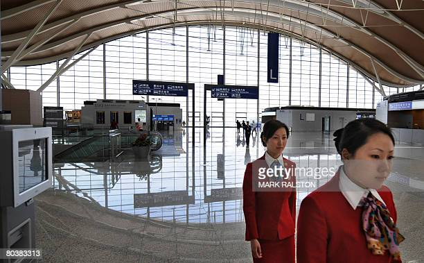 Airline staff are seen in the main departures hall of the new terminal two at the Pudong International Airport in Shanghai on March 26 2008 The new...