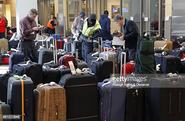 Airline workers and travelers try to sort through all the luggage that is unclaimed at RDU Airport in Morrisville NC Tuesday Jan 7 2014