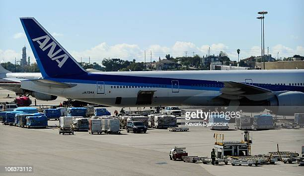 Airline workers load cargo into an All Nippon Airways passenger plane at Los Angeles International Airport on October 30 2010 in Los Angeles...
