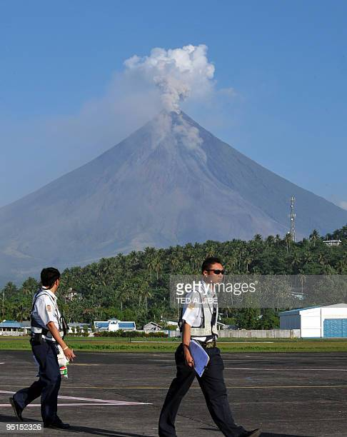 Airline workers walk through the apron as Mayon volcano spews ash into the air at the airport in Legazpi City Albay province southeast of Manila on...