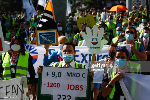 Airline workers wear protective face masks while carrying banners during a protest by Deutsche Lufthansa AG employees and union members outside the...