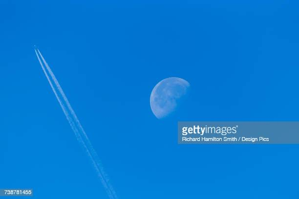 Airliner passing in front of the waning moon