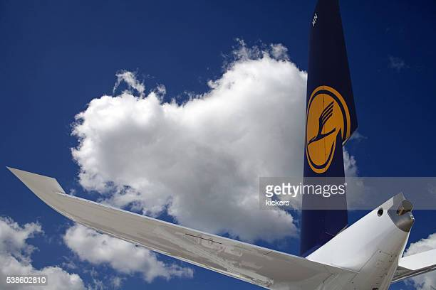 Airliner tail wing in blue summer sky with puffy clouds