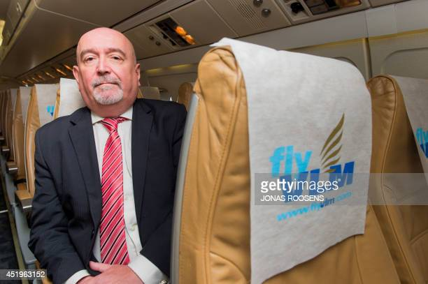 Airlines's CEO, Arthur White poses for a photograph on July 10, 2014 in a VLM plane wearing VLM Airlines' new colors on the occasion of the first...