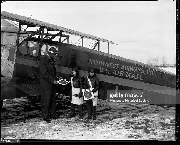 Airmail pilot 'Speed' Holman standing next to his plane accepts a newspaper from a young newsboy