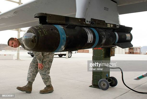 Airman 1st Class Ozzy Toma walks around an inert Hellfire missile as he performs a preflight check on an MQ1B Predator unmanned aircraft system April...