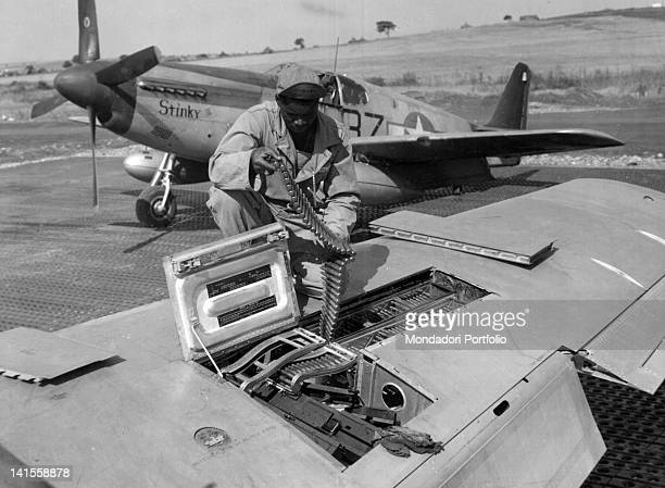 A US airman checks the munitions of a machine gun on the right wing of a North American P51 Mustang Italy March 1944
