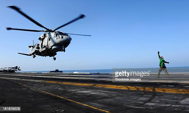 Airman directs an EH-101 Merlin helicopter onto the flight deck of USS John C. Stennis.