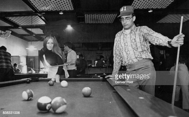 Airman Maurice Forrest Syracuse NY looks on as Bun­ny Patti of the Denver Playboy Club makes a shot during a special pool tournament Sunday at the...