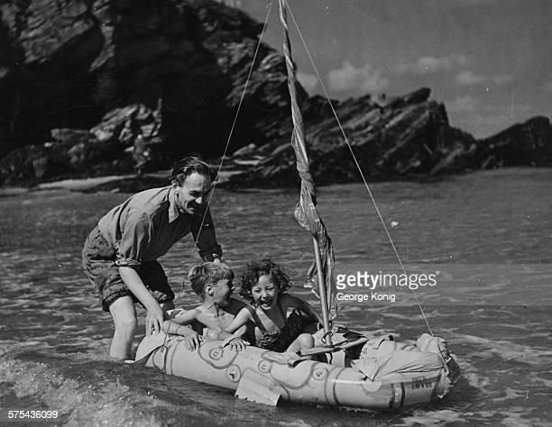Airman Nigel Tangye husband of actress Ann Todd pictured pushing their children David and Francesca in a rubber dinghy in the sea on the coast of...