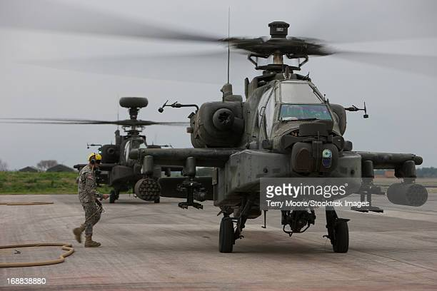 Airman plugging in a communications wire to an AH-64 Apache helicopter prior to refueling, Conroe, Texas.
